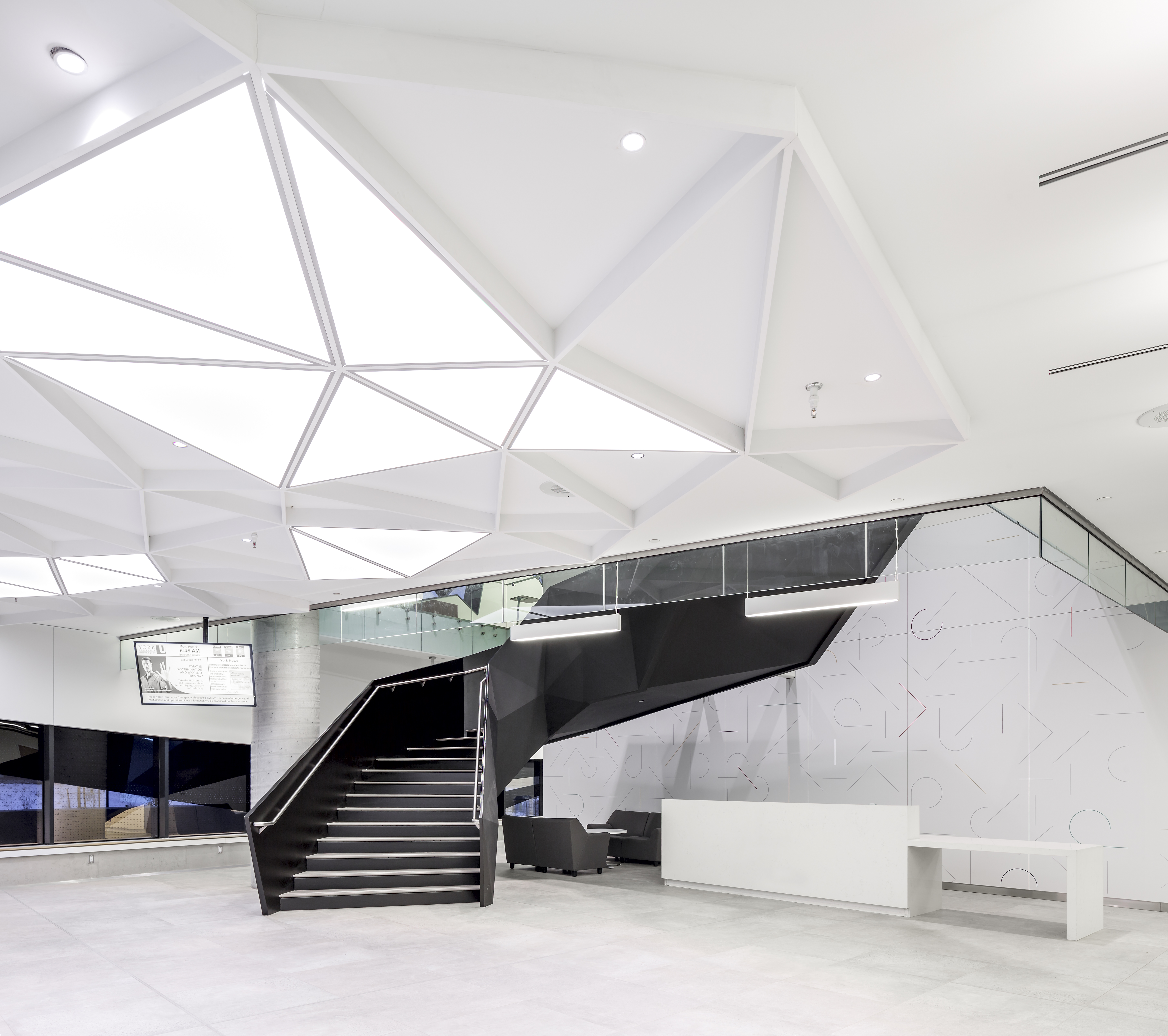 "The dynamic triangle motif carries through the building like a brand icon, visible here in the main lobby's fluorescent ""skylights"" and U-shaped staircase constructed from welded triangular slabs of steel. Photography by Doublespace Photography"