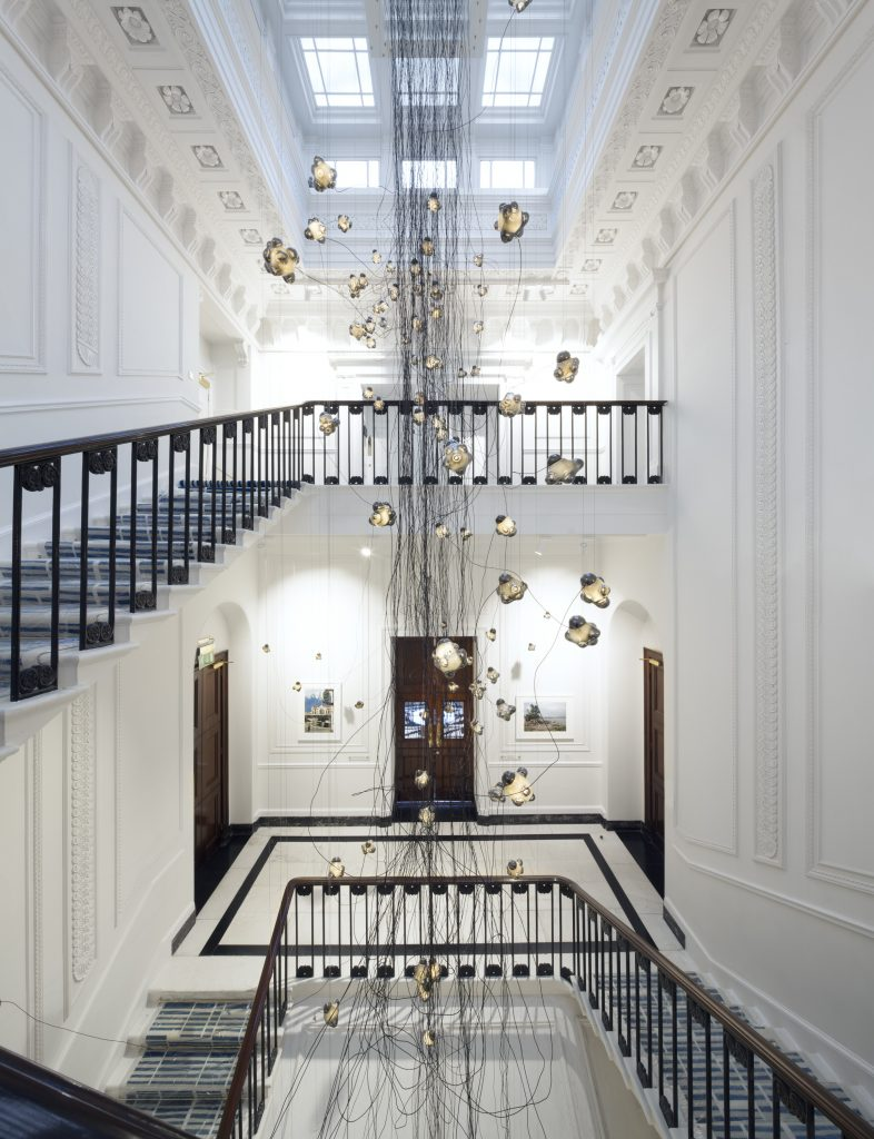 Canada House's original staircase, with its remarkably slim profile given its 1823 date of construction, has been meticulously restored. Omar Arbel of Bocci has contributed 57.157, a 14.5 metre, gossamer-like light fixture of thin wires and supporting glass globes that suggest a whimsical reference to snowflakes. Photo by Ben Blossom.