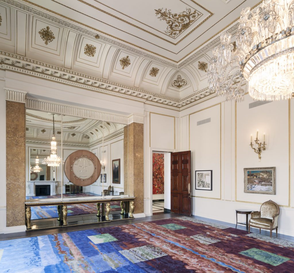 "Originally the High Commissioner's enormous office, the Sir John A. MacDonald Room now serves as a grand reception space with its fireplace restored and neo-classical details highlighted in gild to showcase carefully curated Canadian art work. Its competition winning carpet, ""Foothill,"" is designed by Saskatchewan artist Sean William Randal and translated into a carpet by Toronto's Creative Matters. Photo by Ben Blossom."
