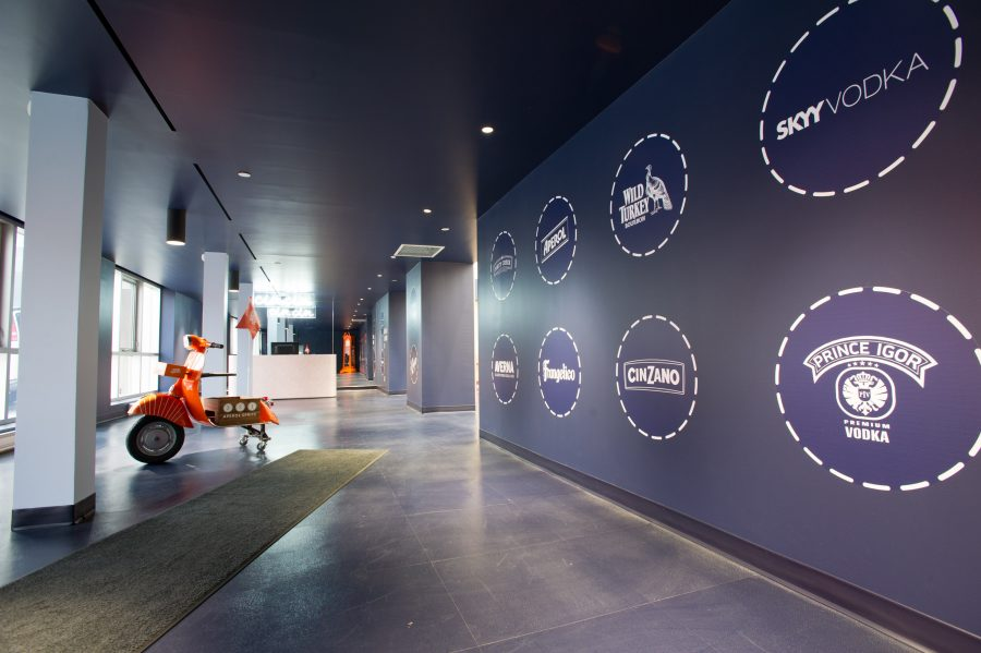 A visitor to the office must first pass through a compressed, dark reception area, similar to a nightclub's cloakroom, adorned with simple Italian icons like a modified Vespa scooter, and the logos of the group's brands. Photography by George Pimental Photography