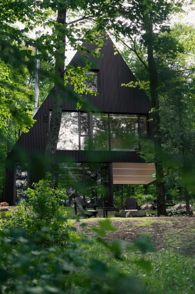 The exaggerated pitch of the roofs and matte black metal siding make the cottage feel like a children's impression of a huge, sheltering spruce tree, rising in the midst of the woods. Photography by Maxime Brouillet