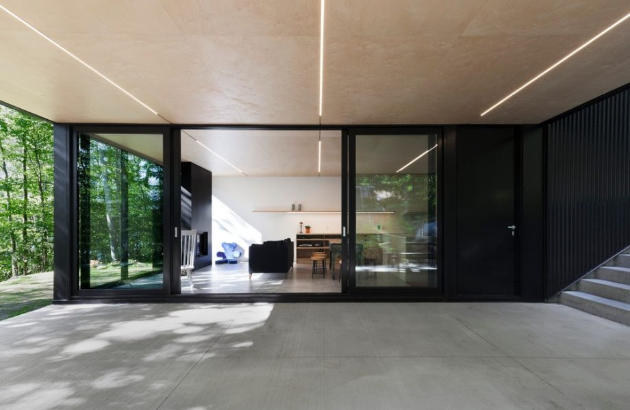 Broad window walls make the seating area feel like part of the forest, rather than merely facing it. Photography by Maxime Brouillet