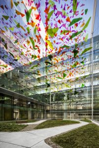 In one courtyard visible to young patients recovering in their care rooms, a wind animated mobile of multi-coloured shards shimmers in the sunlight or from night time illumination.
