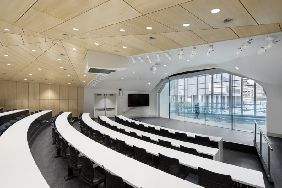 he white upper auditorium hosts presentations and shows for the children under a sculpted ceiling of rich, naturally stained wood. A west-facing glass wall overlooks the atrium but also provides tantalizing views of the brightly coloured exterior play area.