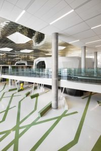 "The atrium's volu-minous space sparkles under a reflective, aluminum-tiled ceiling invoking a cloud flecked sky. Green ""branches"" crisscross the floor, morphing into benches under an interior bridge supported by canted trunk-like columns. Patrick Berubé's bright-coloured ""totem"" figures add a touch of whimsy"